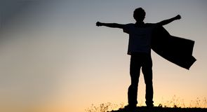Boy playing superheroes on the sky background, silhouette of tee. N superhero in a raincoat on the hill Stock Photography