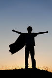 Boy playing superheroes on the sky background, stock photos