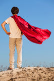 Boy playing superheroes on the sky background, stock photography