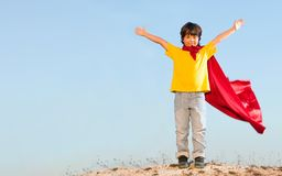 Boy playing superheroes on the sky background, teenage superhero royalty free stock image