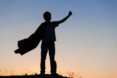 Boy playing superheroes on the sky background, teenage superhero royalty free stock images
