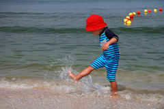 Boy Playing in Surf. Profile of a 2 year old boy kicking water through the surf seaside Royalty Free Stock Image