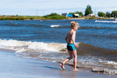 Boy playing in the surf Royalty Free Stock Images