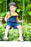 Boy playing swing Stock Images