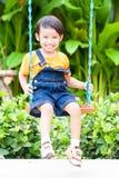 Boy playing swing Stock Photos