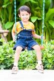 Boy playing swing Royalty Free Stock Photos