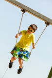 Boy playing swinging by swing-set. Royalty Free Stock Photo