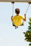 Boy playing swinging by swing-set. Royalty Free Stock Photo