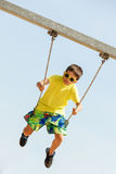 Boy playing swinging by swing-set. Royalty Free Stock Photography