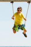 Boy playing swinging by swing-set. Stock Photos