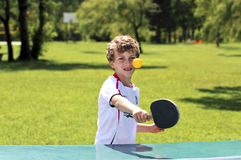 Boy playing table tennis. Outdoor image of boy playing sport Royalty Free Stock Photography