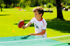 Boy playing table tennis in the park. Outdoor portrait of boy playing table tennis Stock Photography