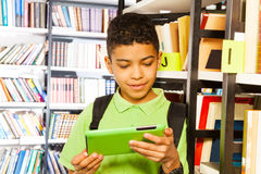 Boy playing with tablet in library. Boy playing with tablet and standing near bookshelf in library Stock Images