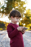 Boy playing on tablet in nature Stock Photography