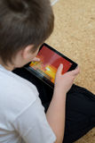 Boy playing on Tablet PC Royalty Free Stock Images
