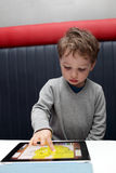 Boy playing with tablet PC Stock Image