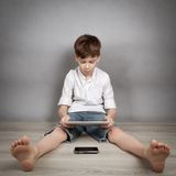 Boy playing on tablet. Portrait of boy, playing on tablet on gray background, indoors, studio portrait on gray background, studio Stock Photo