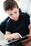 Boy playing on a tablet Stock Images