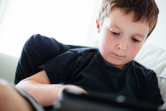 Boy playing on a tablet Royalty Free Stock Photo