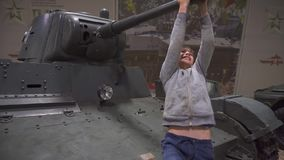 Boy is playing on a tank barrel