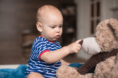 Boy playing with teddy bear. Adorable little boy playing with teddy bear toy Royalty Free Stock Photo