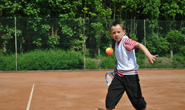 Boy playing tennis. Concentrated boy playing tennis on a gravel court Royalty Free Stock Photography