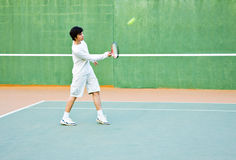 Boy playing tennis. Side view of teenage boy playing tennis on court Stock Image