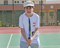 The Boy is Playing Tennis. In the Tennis Court Royalty Free Stock Photography