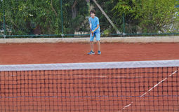 Boy is playing tennis. In the tennis court Stock Images