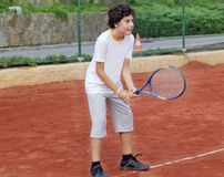Boy is playing tennis. In the tennis court Stock Photo