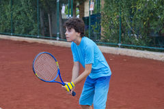 Boy is playing tennis. In the tennis court Royalty Free Stock Photography