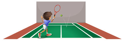 A boy playing tennis at the court Stock Photos