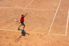 The boy plays tennis on the orange dirt court. Court hard. Boy playing tennis on a dross court, The boy plays tennis on the orange dirt court. Court hard. Young stock photos