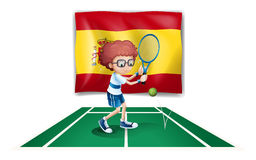 A boy playing tennis in front of the flag of Spain Stock Photo