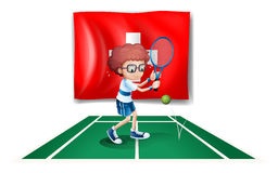 A boy playing tennis in front of the Switzerland flag Royalty Free Stock Photo