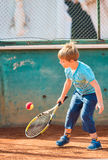 Boy playing tennis. Little boy playing tennis outdoors on the tennis field on a sunny day Royalty Free Stock Photography