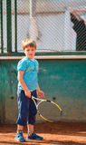 Boy playing tennis. Little boy playing tennis outdoors on the tennis field on a sunny day Stock Photo