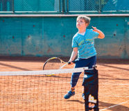 Boy playing tennis. Little boy playing tennis outdoors on the tennis field on a sunny day Royalty Free Stock Photo