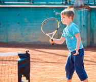Boy playing tennis. Little boy playing tennis outdoors on the tennis field on a sunny day Stock Photos