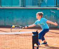 Boy playing tennis. Little boy playing tennis outdoors on the tennis field on a sunny day Royalty Free Stock Images