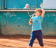 Boy playing tennis. Little boy playing tennis outdoors on the tennis field on a sunny day Stock Image
