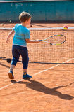 Boy playing tennis. Little boy playing tennis outdoors on the tennis field on a sunny day Royalty Free Stock Photos