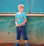 Boy playing tennis. Little boy playing tennis outdoors on the tennis field on a sunny day Stock Images