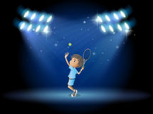 A boy playing tennis in the middle of the stage Stock Photos