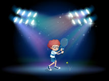 A boy playing tennis with spotlights Royalty Free Stock Photography