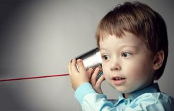 Boy Playing with Tin Can Phone. Isolated on grey Background.  stock photo
