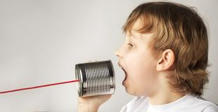Boy Playing with Tin Can Phone. Isolated on Orange Background.  royalty free stock photo