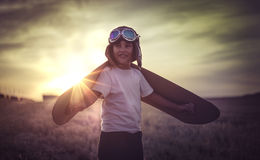 Boy playing to be a classic pilot, wearing a fur hat, glasses an Royalty Free Stock Images