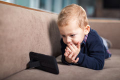 Boy playing and touching a mobile phone Stock Images