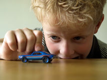 Boy playing with toy car. Little boy playing with blue toy car on the table Royalty Free Stock Images